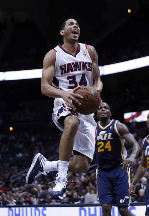 Atlanta Hawks point guard Devin Harris (34) goes to the basket as Utah Jazz power forward Paul Millsap (24) looks on in the second half of an NBA basketball game on Friday, Jan. 11, 2013, in Atlanta. Atlanta won 103-95. (AP Photo/John Bazemore)