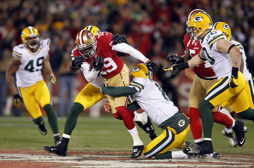San Francisco 49ers wide receiver Ted Ginn Jr. (19) is tackled by Green Bay Packers linebacker Terrell Manning, rear, and punter Tim Masthay (8) during the first quarter of an NFC divisional playoff NFL football game in San Francisco, Saturday, Jan. 12, 2013. (AP Photo/Tony Avelar)