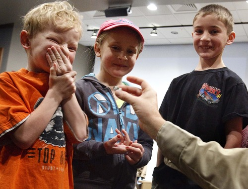 Leah Hogsten  |  The Salt Lake Tribune A shy Corbin Draper, 5, left, of Hooper, giggles after his Barred Owl call wins him an owl figurine for his efforts at the Bear River Migratory Bird Refuge's Owl Day on Saturday in Brigham City.