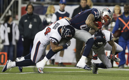 New England Patriots tight end Aaron Hernandez is tackled by Houston Texans linebacker Barrett Ruud (54) and Johnathan Joseph, right, during the first half of an AFC divisional playoff NFL football game in Foxborough, Mass., Sunday, Jan. 13, 2013. (AP Photo/Elise Amendola)