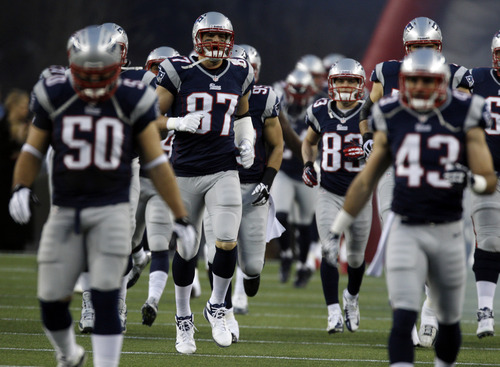 New England Patriots tight end Rob Gronkowski (87) runs onto the field with his teammates before an AFC divisional playoff NFL football game against the Houston Texans in Foxborough, Mass., Sunday, Jan. 13, 2013. (AP Photo/Charles Krupa)