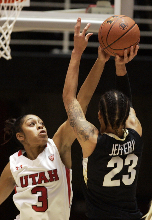 Kim Raff | The Salt Lake Tribune University of Utah player (left) Iwalani Rodrigues gets a piece of  the ball as Colorado player Chucky Jeffrey takes a shot during a game at the Huntsman Center in Salt Lake City on January 13, 2013. Utah lost the game 43-56.
