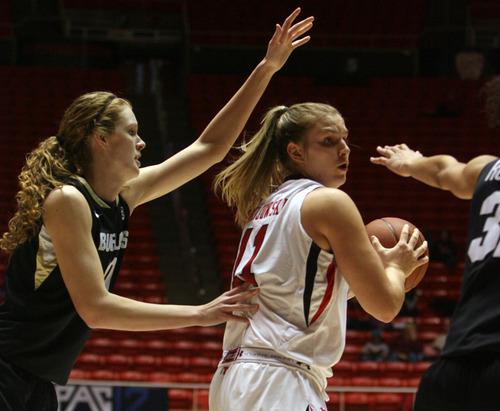 Kim Raff | The Salt Lake Tribune University of Utah player (middle) Taryn Wicijowski looks to pass past Colorado player (left) Rachel Hargis during a game at the Huntsman Center in Salt Lake City on January 13, 2013. Utah lost the game 43-56.