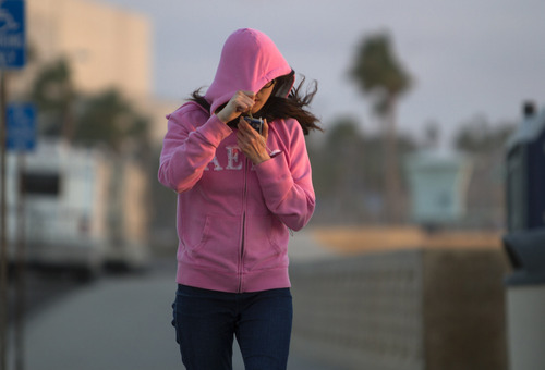 Fiona Chiang shields her face from blowing sand as she walks north on Carlsbad Boulevard in Carlsbad, Calif. Thursday, Jan. 10, 2013. Southern California is bracing for a cold snap that is expected to drop temperatures to a six-year low. (AP Photo/U-T San Diego, Bill Wechter)  SAN DIEGO COUNTY OUT; NO SALES; COMMERCIAL INTERNET OUT; FOREIGN OUT