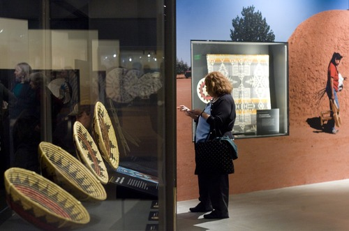 "Kim Raff  |  The Salt Lake Tribune Elsie Garcia reads a display in ""A Celebration of Contemporary Navajo Baskets"" exhibit, which opened at the Natural History Museum of Utah in Salt Lake City on January 12, 2013. The exhibit features more than 150 works of art created by the basket weavers of Monument Valley, Utah."