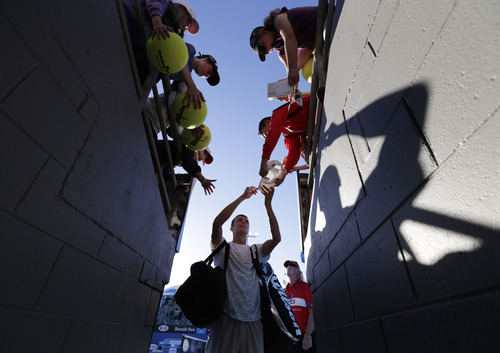 Russia's Andrey Kuznetsov signs autographs after winning his first round match against Argentina's Juan Monaco at the Australian Open tennis championship in Melbourne, Australia, Monday, Jan. 14, 2013. (AP Photo/Andy Wong)