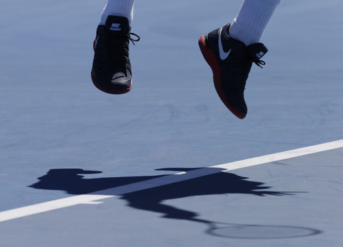 Tomas Berdych of the Czech Republic is airborne as he serves to Michael Russell of the US during their first round match at the Australian Open tennis championship in Melbourne, Australia, Monday, Jan. 14, 2013. (AP Photo/Andy Wong)