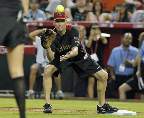 FILE - In this July 10, 2011 file photo, former Arizona Diamondbacks baseball player and television analyst Mark Grace takes a throw at first base during the MLB All-Star Celebrity softball game in Phoenix. Grace says he blames himself, not the team, for firing him last season. The former first baseman with the Diamondbacks and the Chicago Cubs was fired after he was arrested last August in Scottsdale _ his second drunken driving arrest in 15 months. (AP Photo/Ross D. Franklin, File)