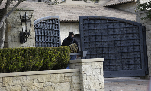 """An unidentified man enters a gate at the home of cyclist Lance Armstrong, Monday, Jan. 14, 2013, in Austin, Texas. After more than a decade of denying that he doped to win the Tour de France seven times, Armstrong was set to sit down Monday for what has been trumpeted as a """"no-holds barred,"""" 90-minute, question-and-answer session with Oprah Winfrey. (AP Photo/Eric Gay)"""