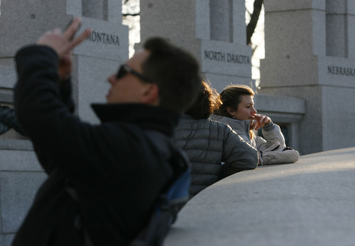 Scott Sommerdorf   |  The Salt Lake Tribune A man photographs the Utah column as visitors to the World War II Memorial pause to take in the sight. A tour of D.C. for travelers from Utah, Friday, January 4, 2013.