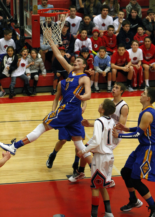 Chris Detrick     The Salt Lake Tribune Orem's Jordan Darger (10) shoots past Springville's Spencer Frixione (1)  during the game at Springville High School Friday January 11, 2013.