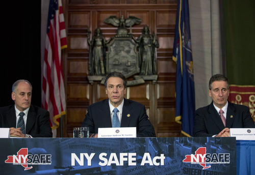 New York Gov. Andrew Cuomo, center, speaks during a news conference announcing an agreement with legislative leaders on New York's Secure Ammunition and Firearms Enforcement Act in the Red Room at the Capitol on Monday, Jan. 14, 2013, in Albany, N.Y. Also pictured are Secretary to the Governor Larry Schwartz, left, and Lt. Gov. Robert Duffy. (AP Photo/Mike Groll)