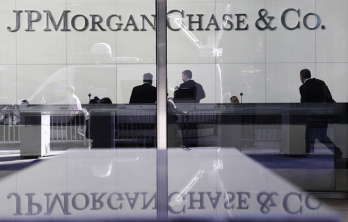 FILE - In this May 11, 2012 file photo, people stand in the lobby of JPMorgan Chase headquarters in New York. JPMorgan Chase reported a 55 percent jump in earnings for the last three months of 2012 as mortgage fees and other income surged. (AP Photo/Mark Lennihan, File)
