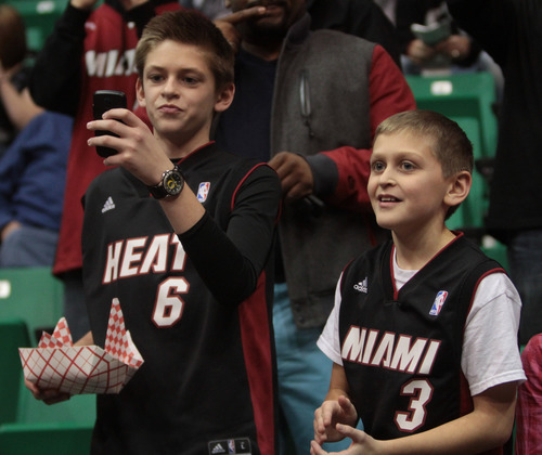 Rick Egan  | The Salt Lake Tribune   Miami Heat fans sneak down to the front to get a peak at their favorite players during warms up before the Utah Jazz, Miami Heat game at EnergySolutions Arena, Monday, January 14, 2013.