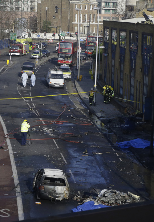 Remnants of a helicopter, bottom right, which crashed onto a construction crane are seen on the ground by a burnt out car in London, Wednesday, Jan. 16, 2013. The helicopter crashed into a crane and fell on a crowded street in central London during rush hour Wednesday, sending black plumes of smoke into the air as it smashed to the ground. The pilot and one person on the ground were killed and 13 others injured, officials said. (AP Photo/Lefteris Pitarakis)