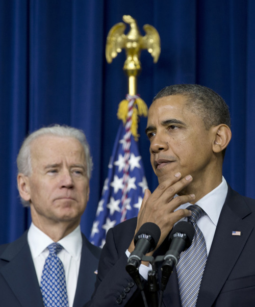 President Barack Obama, accompanied by Vice President Joe Biden, pauses as he talked about proposals to reduce gun violence, Wednesday, Jan. 16, 2013, in the South Court Auditorium at the White House in Washington. (AP Photo/Carolyn Kaster)