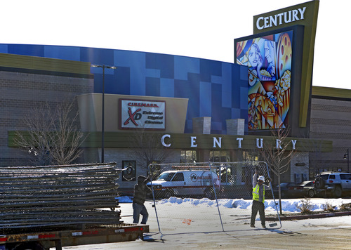 """Workers with American Fence remove the fence from around the Century theater in Aurora, Colo., on Thursday, Jan. 17, 2013.  The Colorado movie theater where a gunman killed 12 people and wounded dozens of others reopens Thursday with a private ceremony for victims, first responders and officials.   Theater owner Cinemark plans to temporarily reopen the entire 16-screen complex in Aurora to the public on Friday, then permanently on Jan. 25. Aurora's mayor, Steve Hogan, has said residents overwhelmingly support reclaiming what he calls """"an important venue for Aurora.""""  (AP Photo/Ed Andrieski)"""