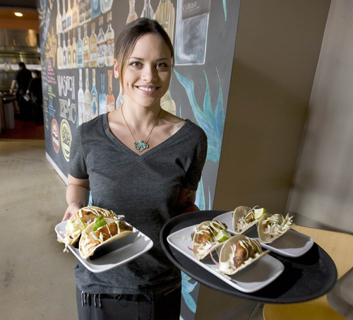 Paul Fraughton  |  The Salt Lake Tribune Server Stephanie Sims delivers fish tacos to diners at Taqueria 27 in Salt Lake City.