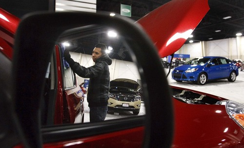 Leah Hogsten     The Salt Lake Tribune Alexander Jerez cleans the window of a Nissan Versa on the showroom floor Thursday January 17, 2013 in Sandy. The Utah International Auto Expo starts tomorrow at the South Towne Expo Center.