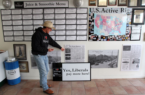 """Francisco Kjolseth     The Salt Lake Tribune George Burnett, owner of Covers & Camo in Vernal Utah where he sells custom seat covers along with apparel and stickers with the slogan """"I (Heart) Drilling!"""", proudly points out some of the history he's dug up in Vernal's oil and gas drilling. A few weeks back Burnett started a new venture and a new controversy. Added to his shop is the I Love Drilling Juice & Smoothie Bar where liberals pay extra. As Burnett puts it """"liberal policies are costing us more,"""" and so if you admit to being liberal you can expect to pay more for your drink."""
