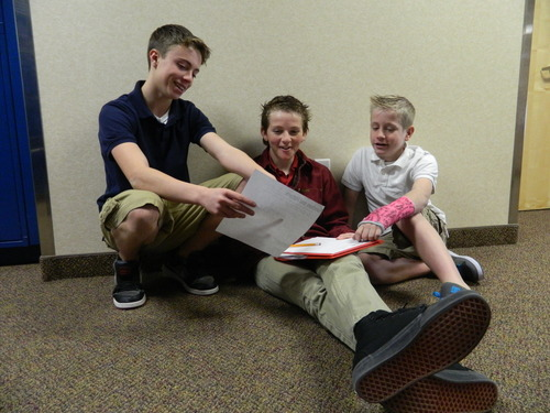 Tyce Petterson, right, Spencer Vockel and Lucas Stowe look over school work at Syracuse Arts Academy. Petterson won a statewide contest for his video essay about Martin Luther King, Jr. Carol Lindsay | Special to The Tribune