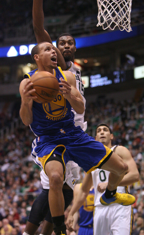 Steve Griffin | The Salt Lake Tribune   Golden State's Stephen Curry gets to the basket  as Utah's Derrick Favors tries to block his shot during second half action of the Utah Jazz Versus Golden State Warriors game at EnergySolutions Arena in Salt Lake City, Utah Wednesday December 26, 2012.