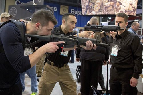 Firearms instructors Logan Martin, left, and Andres Gonzalez, of Calgary, Alberta, look through the sights of Sig Sauer Swat Patrol AR rifles during the 35th annual SHOT Show, Tuesday, Jan. 15, 2013, in Las Vegas. (AP Photo/Julie Jacobson)
