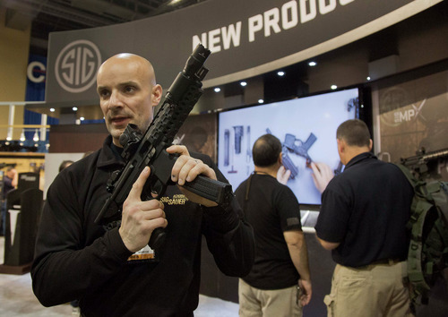 Sig Sauer representative Adam Painchaud explains one of the company's newest products, the MPX 9mm pistol caliber submachine gun at the 35th annual SHOT Show, Tuesday, Jan. 15, 2013, in Las Vegas. The National Shooting Sports Foundation was focusing its trade show on products and services new to what it calls a $4.1 billion industry, with a nod to a raging national debate over assault weapons. The gun is for military and law enforcement use and not available for sale to the public. (AP Photo/Julie Jacobson)
