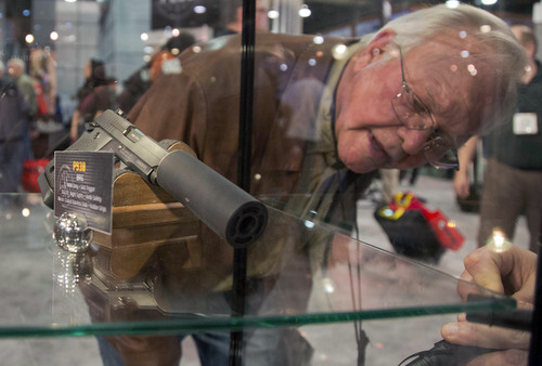 A convention attendee looks through a Sig Sauer display case of various guns including a P938 Nightmare 9mm semiautomatic pistol at the 35th annual SHOT Show, Tuesday, Jan. 15, 2013, in Las Vegas. The National Shooting Sports Foundation was focusing its trade show on products and services new to what it calls a $4.1 billion industry, with a nod to a raging national debate over assault weapons. (AP Photo/Julie Jacobson)