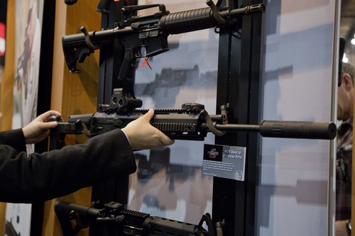 Accessories manufacturer Kevin Kao, of Irvine, Calif., examines a military grade Remington ACR Special Purpose Rifle at the 35th annual SHOT Show, Tuesday, Jan. 15, 2013, in Las Vegas. The National Shooting Sports Foundation was focusing its 35th annual SHOT Show on products and services new to what it calls a $4.1 billion industry, with a nod to a raging national debate over assault weapons.  (AP Photo/Julie Jacobson)