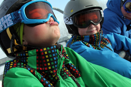 Francisco Kjolseth  |  The Salt Lake Tribune Visiting from South Carolina, Connor Flannigan, 6, left, tries to catch snowflakes alongside his twin brother, Thomas, and family friend, John Beasley, of Sandy, as they ride the Payday lift at Park City Mountain Resort on the last day of 2012.