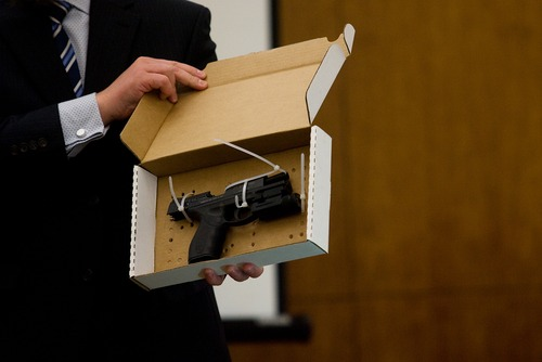 Mark Johnston  |  Daily Herald  Detective Zach Adams shows the jury a pistol during the trial of Martin Bond in 4th District Court in American Fork Friday, Jan. 18, 2013. On Friday a jury convicted Bond of killing former BYU professor Kay Mortensen in November 2009.