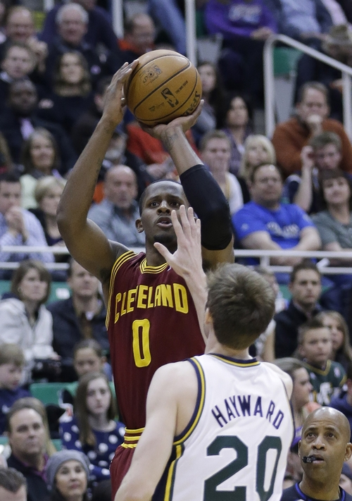 Cleveland Cavaliers' C.J. Miles (0) shoots as Utah Jazz's Gordon Hayward (20) defends in the first quarter during an NBA basketball game Saturday, Jan. 19, 2013, in Salt Lake City. (AP Photo/Rick Bowmer)