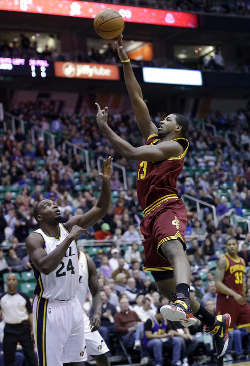 Cleveland Cavaliers forward Tristan Thompson (13) shoots as Utah Jazz forward Paul Millsap (24) looks on in the first quarter during an NBA basketball game Saturday, Jan. 19, 2013, in Salt Lake City. (AP Photo/Rick Bowmer)