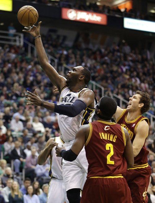 Utah Jazz's Al Jefferson, left, shoots as Cleveland Cavaliers' Kyrie Irving (2) and teammate Luke Walton, right, look on in the third quarter during an NBA basketball game Saturday, Jan. 19, 2013, in Salt Lake City.  The Jazz defeated the Cavaliers 109-98. (AP Photo/Rick Bowmer)