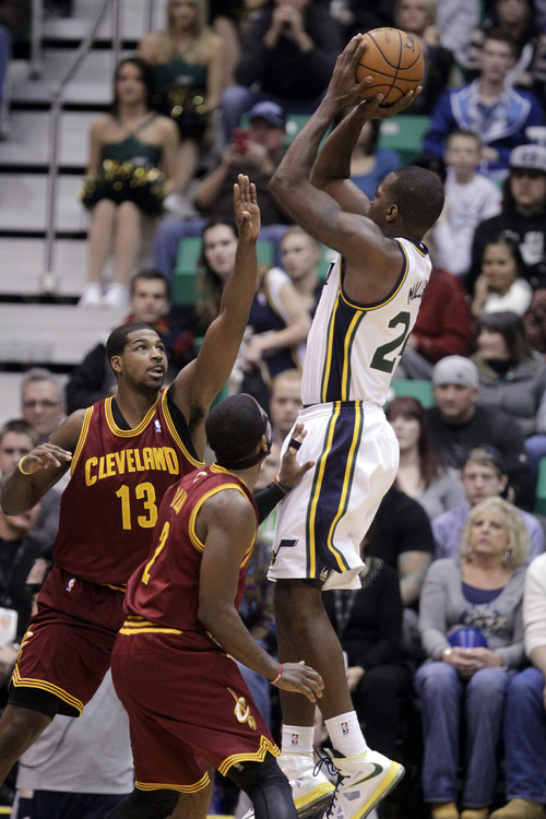 Cleveland Cavaliers forward Tristan Thompson (13) defends against Utah Jazz forward Paul Millsap (24) as he shoots while Cleveland Cavaliers guard Kyrie Irving (2) looks on in the first quarter during an NBA basketball game Saturday, Jan. 19, 2013, in Salt Lake City. (AP Photo/Rick Bowmer)