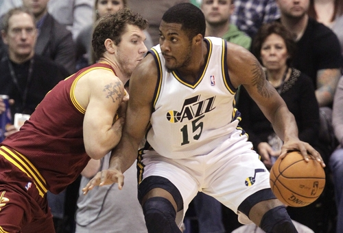 Cleveland Cavaliers forward Luke Walton, left, defends against Utah Jazz forward Derrick Favors (15) in the second quarter during an NBA basketball game Saturday, Jan. 19, 2013, in Salt Lake City. (AP Photo/Rick Bowmer)