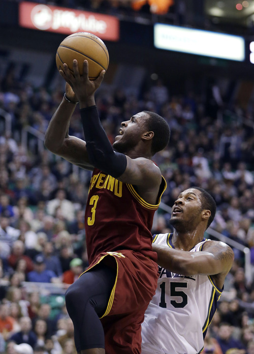 Cleveland Cavaliers guard Dion Waiters (3) goes to the basket as Utah Jazz forward Derrick Favors (15) looks on in the second quarter during an NBA basketball game Saturday, Jan. 19, 2013, in Salt Lake City. (AP Photo/Rick Bowmer)