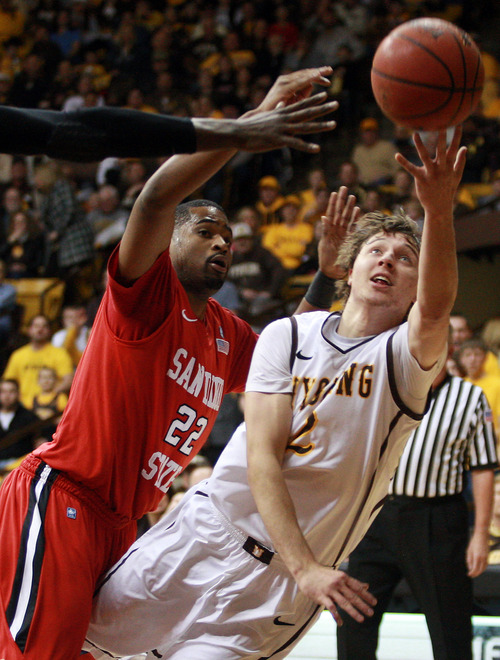 Wyoming's Riley Grabau, right, forces a shot as he is fouled by San Diego State's Chase Tapley during an NCAA college basketball game Saturday, Jan. 19, 2013, in Laramie, Wyo. (AP Photo/Casper Star-Tribune, Alan Rogers)