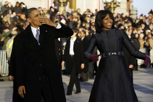 President Barack Obama blows a kiss as he and first lady Michelle Obama walk on Pennsylvania Avenue near the White House in the Inauguration Parade during the 57th Presidential Inauguration in Washington, Monday, Jan. 21, 2013. (AP Photo/Charles Dharapak)