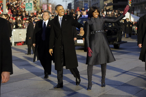 President Barack Obama and first lady Michelle Obama walk in the Inauguration Parade near the White House during the 57th Presidential Inauguration in Washington, Monday, Jan. 21, 2013. (AP Photo/Charles Dharapak)