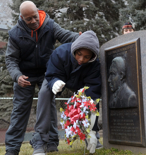 Frankie West, left, watches Amadeus Cannon, right, lay a wreath at a memorial during the Martin Luther King Civil Rights Movement March at Martin Luther King Park in Bethlehem, Pa. on Monday, Jan. 21, 2013. (AP Photo/The Express-Times, Matt Smith)