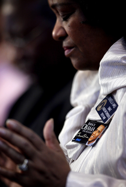 Sen. Donzella James, D-College Park, wears a President Barack Obama pin as she prays during the annual Dr. Martin Luther King Jr. holiday commemorative service at the Ebenezer Baptist Church, Monday, Jan. 21, 2013, in Atlanta. The nation will honor civil rights leader Martin Luther King Jr. on Monday, the same day as it celebrates the inauguration of the first black president to his second term. (AP Photo/David Goldman)