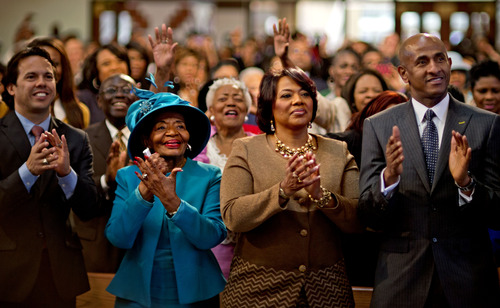 Bernice King, center right, and Christine King Farris, center left, the daughter and sister of Dr. Martin Luther King Jr., applaud while watching a broadcast as President Barack Obama is inaugurated following the Dr. Martin Luther King Jr. holiday commemorative service at the Ebenezer Baptist Church in Atlanta Monday, Jan. 21, 2013. (AP Photo/David Goldman)