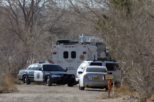 BCSO Deputies and crime scene personnel work the scene of a five person homicide in Albuquerque, NM, Sunday Jan. 20, 2013. Authorities said a teenage boy fatally shot two adults and three children at a home near Albuquerque. (AP Photo/Albuquerque Journal, Pat Vasquez-Cunningham)