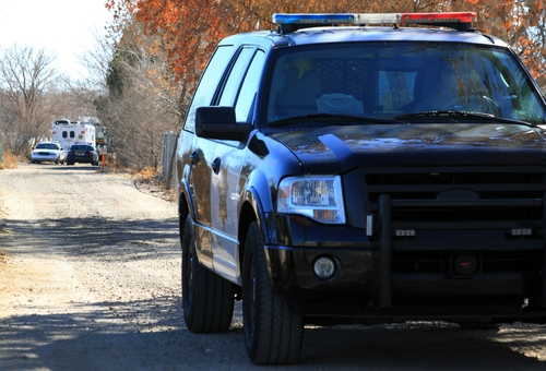A Bernalillo County sheriff's deputy blocks the dirt road that leads to a home where detectives on Sunday, Jan. 20, 2013, were investigating the deaths of five people who were shot to death south of Albuquerque, N.M. Authorities say a teenager has been arrested and booked on murder and other charges in connection with the shootings. (AP Photo/Susan Montoya Bryan)
