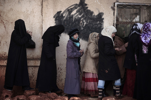 FILE - In this Wednesday, Dec. 12, 2012, file photo, Syrian women wait outside a bakery shop to buy bread in Maaret Misreen, near Idlib, Syria. As the civil war drags on, Syria's economy is buckling under the strain of severe shortages and Syrians now spend hours in line every day for a few loaves of bread and petrol at soaring prices. (AP Photo/Muhammed Muheisen, File)