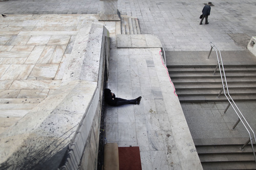A homeless man sits near the closed entrance of a Metro station in central Syntagma square during a strike held by the unions of metro services in Athens, Tuesday, Jan. 22, 2013. Striking subway workers in Athens defied a court order to return to work and continued their protest for a sixth day on Tuesday, as demonstrations against new pay cuts escalated in the Greek capital. (AP Photo/Petros Giannakouris)