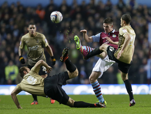 Aston Villa's James Collins, second right, attempts to control the ball as Bradford City' Nahki Wells, right, and teammate James Hanson put him under pressure during their English League Cup second leg semi-final soccer match at Villa's stadium in Birmingham, England, Tuesday, Jan. 22,2013.(AP Photo/Alastair Grant)