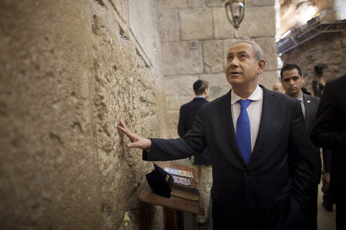 Israeli Prime Minister Benjamin Netanyahu touches the stones of the Western Wall, the holiest site where Jews can pray, in Jerusalem's Old City, on election day, Tuesday, Jan. 22, 2013.Israelis headed to polling stations Tuesday to cast votes in a parliamentary election expected to return  Netanyahu to office despite years of stalled peacemaking with the Palestinians and mounting economic troubles. (AP Photo/Uriel Sinai, Pool)